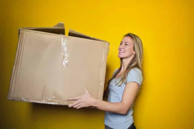 A woman holding a cardboard box