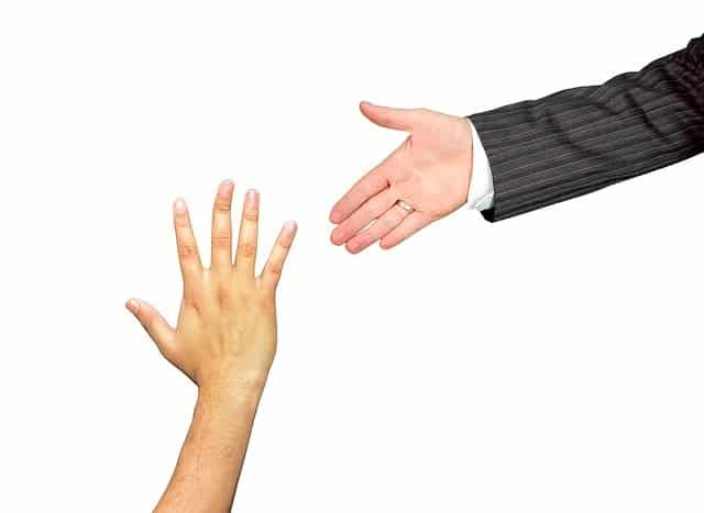 A hand reaching up for assistance, and another hand going towards it.