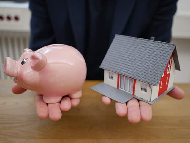 a person holding a piggy bank and a small house