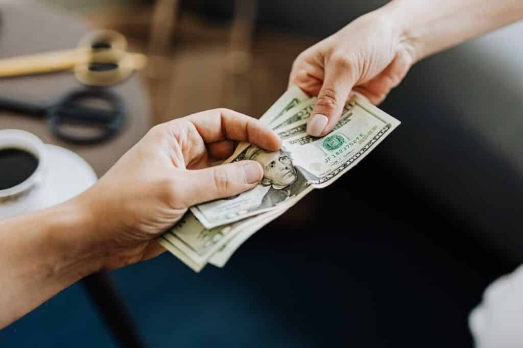 A person handling money to another person